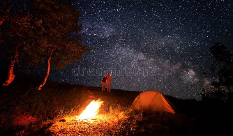 Campa brand och tält under den fantastiska stjärnklara himlen med lotten av glänsande stjärnor arkivfoto