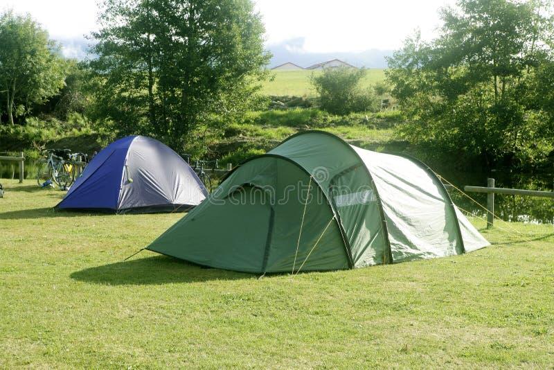 campa fältgräsgreen över tenten arkivfoton