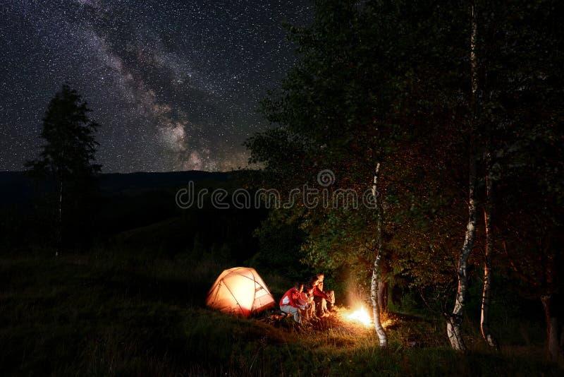 Campa för natt Vänner vid lägereldsammanträde på journaler bland träd near tältet under stjärnklar himmel arkivfoto