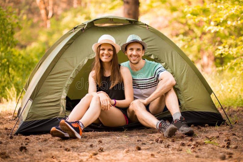 Campa, lopp, turism, vandring och folkbegrepp - lyckligt par i hatt i tält arkivbild
