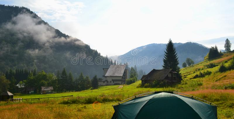 Campa på gräsmattan nära huset på trädgård Bergby bland kufberg royaltyfria bilder