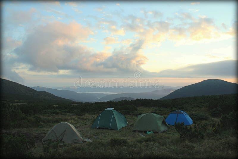Campa tält och hög Mountain View skymningpanorama av fanbergdalen med det alpina lägret vaggar på moränförgrund royaltyfri bild
