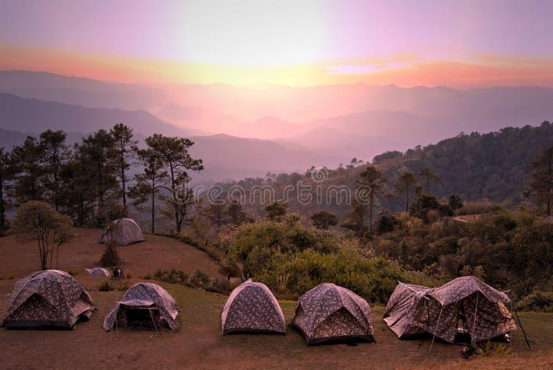 Campa tält på överkanten av berget under härlig solnedgång arkivbilder