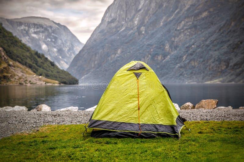 Campa tält sjö en kust på för den sceniska lösa fjorden, med bergskedja i bakgrund - Norge arkivbilder