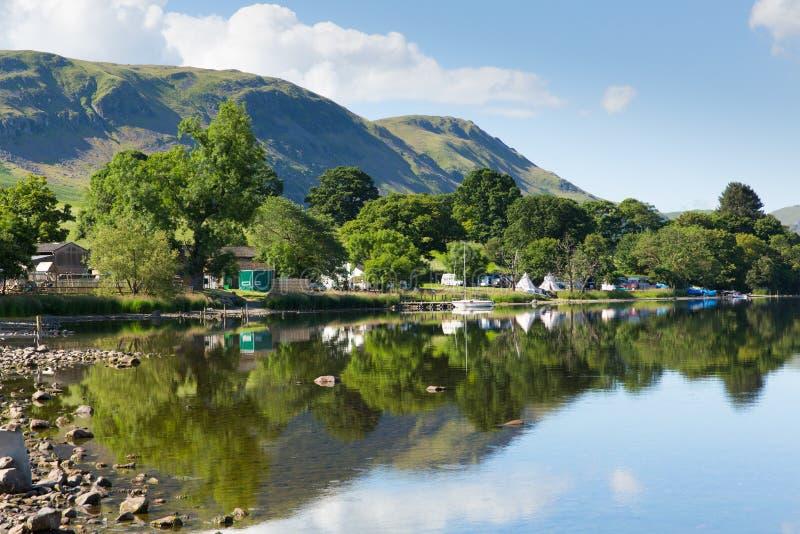 Campa Ullswater sjöområde Cumbria England UK med berg och blå himmel på härlig dag arkivfoto