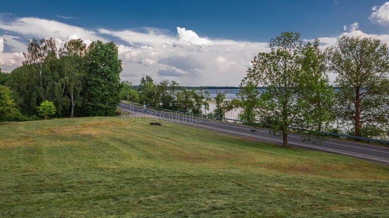 Campagne d'été Vue d'une colline en pente sur une route goudronnée de pays le long de la côte d'un grand lac images libres de droits