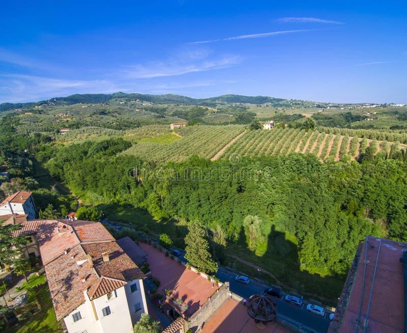 Campagne toscane avec des vignobles, des oliviers, des bois, des fermes et la ville photos stock