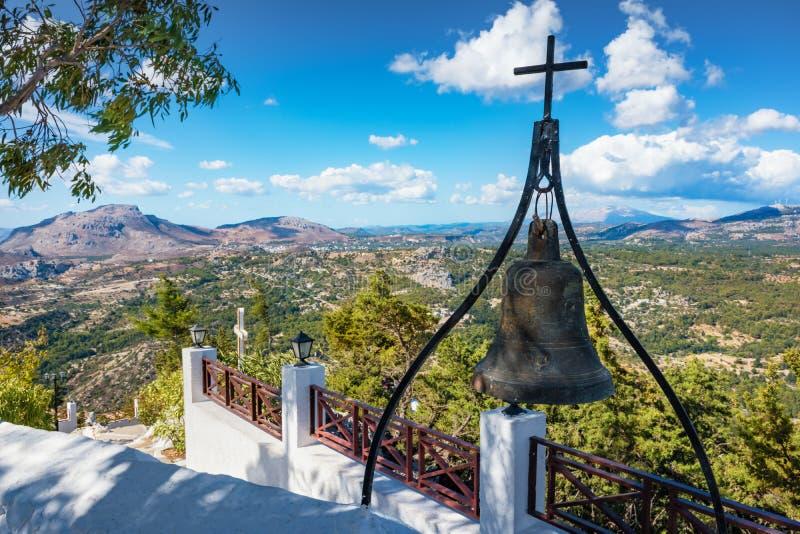 Campana de bronce con la cruz en la pared del monasterio de Tsambika, RODAS, G fotografía de archivo