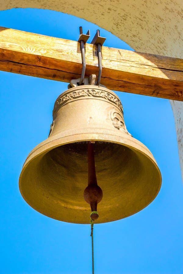 Campana de cobre en el campanario de la iglesia ortodoxa en la parte posterior fotografía de archivo