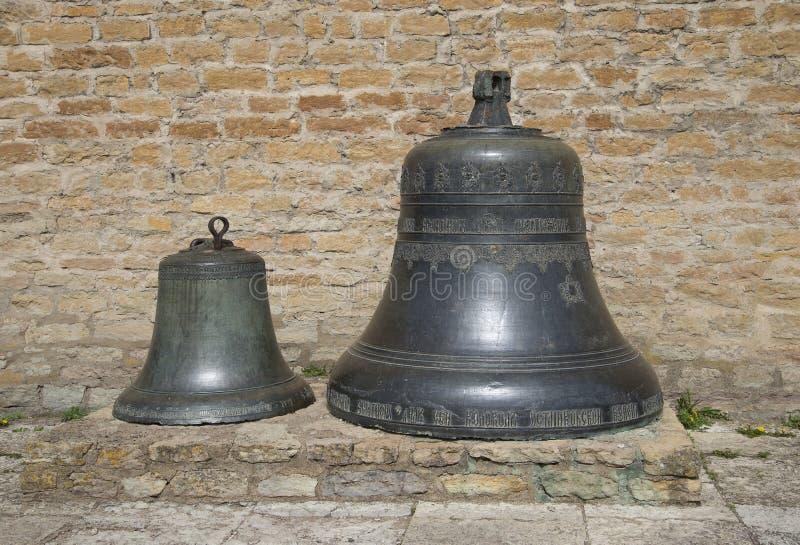 Campana de dos vintages contra la pared del castillo de Herman Narva, Estonia imagen de archivo