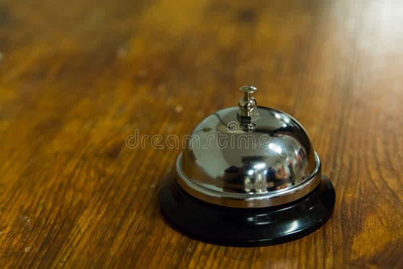 Campana de llamada de servicio de hotel en el mostrador de la recepción de madera imágenes de archivo libres de regalías