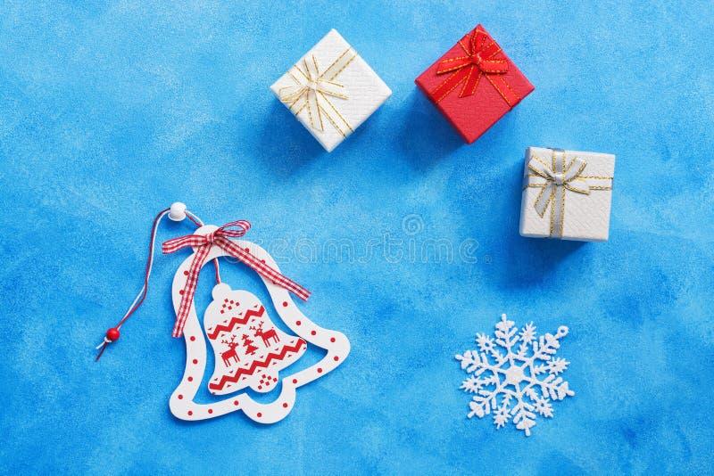 Campana de madera de la Navidad, caja de regalos, copo de nieve en un fondo azul Visión superior, espacio de la copia Endecha pla imágenes de archivo libres de regalías