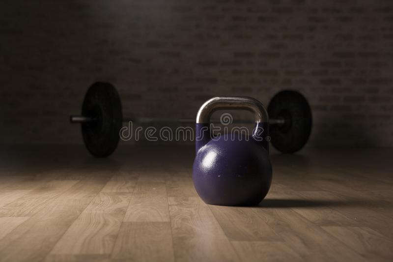 Campana del bollitore e barra di sollevamento pesi su una palestra di legno del pavimento fotografia stock