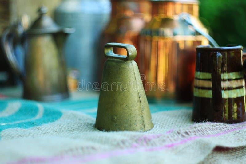 Campana di chiamata, brocche del metallo e bidoni di latte antichi sulla tovaglia di tela fotografia stock libera da diritti