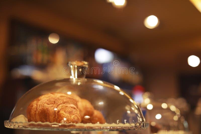 Campana di vetro e piatto di vetro con i croissant sul contatore in caff? fotografia stock