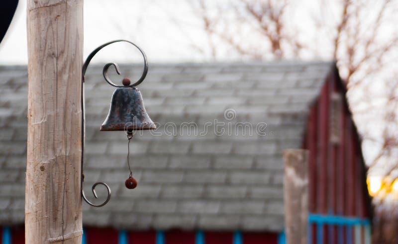 Campana nera del metallo su una posta immagini stock