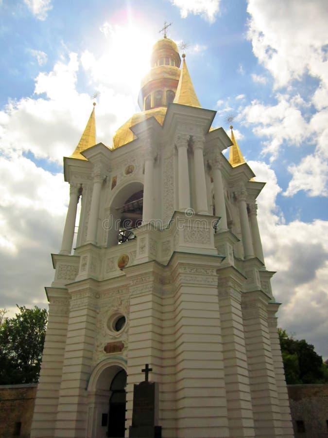 Campanario de Kiev-Pechersk Lavra con el sol brillante en el cielo azul con las nubes blancas foto de archivo