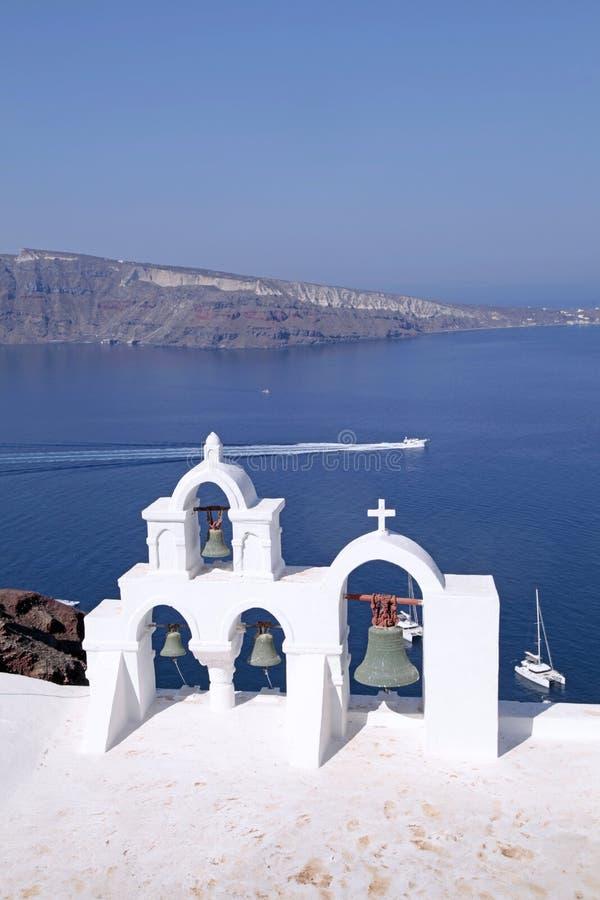 Campanario de la iglesia blanca sobre el mar azul, Santorini, Grecia imagenes de archivo