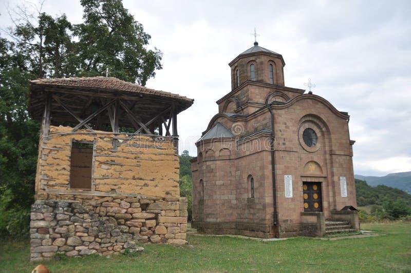 Campanario de madera viejo con la iglesia ortodoxa en lado derecho fotos de archivo libres de regalías