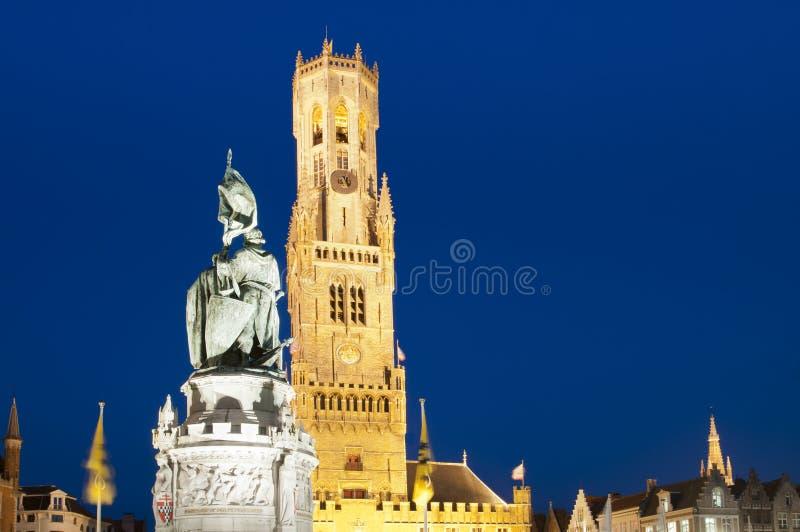 Campanario de una iglesia y mercado de Brujas en la noche, Bélgica. fotografía de archivo