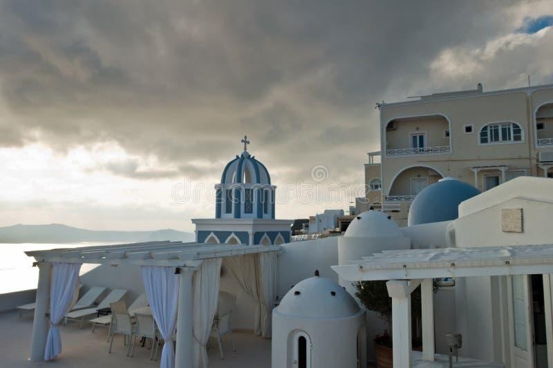Campanario y bóveda azul de una iglesia debajo del cielo dramático en la puesta del sol, pueblo de Imerovigli, isla de Santorini fotografía de archivo libre de regalías