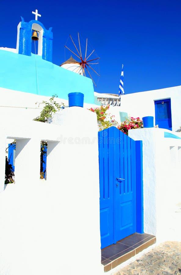 Campanario y molino de viento azules y blancos en el pueblo de Oia, Santorini imagen de archivo