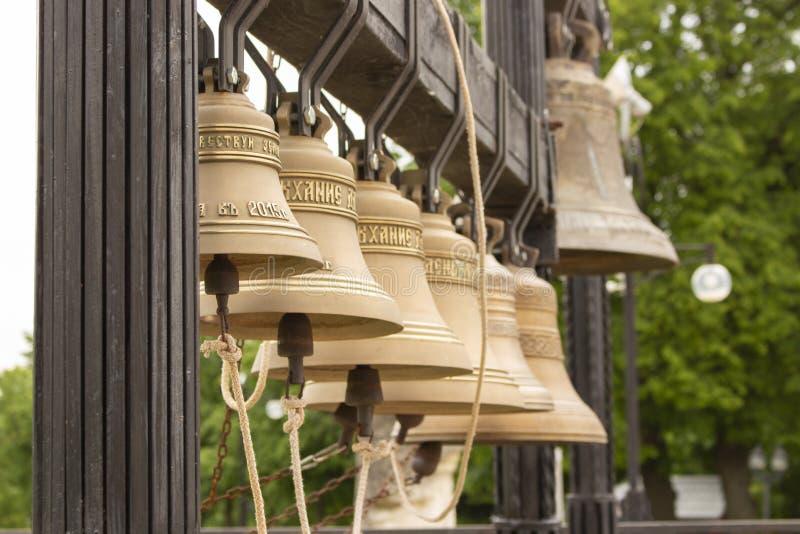 Campanas de iglesia de cobre amarillo de cobre del metal cerca del templo Monasterio cristiano ortodoxo del campanero del instrum fotografía de archivo