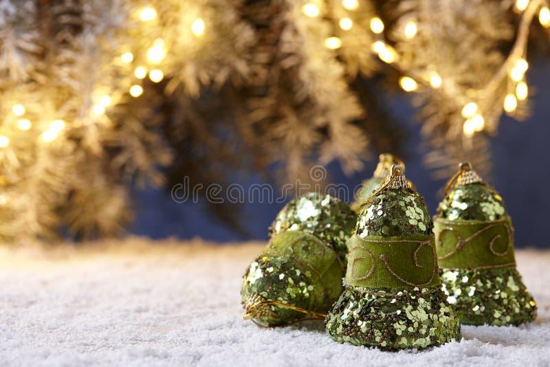 Campanas de la Navidad en la tabla nevosa en fondo de las luces del árbol imagenes de archivo