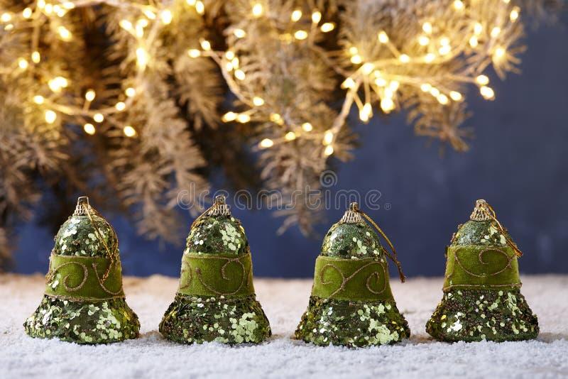 Campanas de la Navidad en la tabla nevosa en fondo de las luces del árbol fotos de archivo