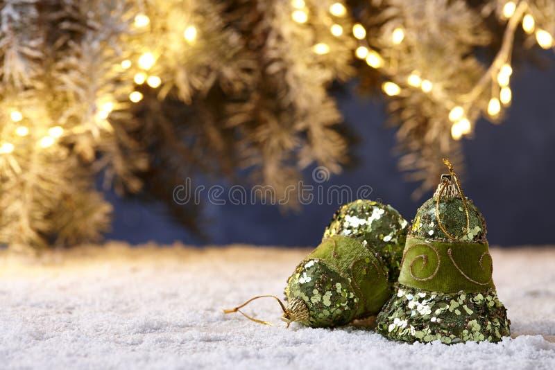 Campanas de la Navidad en la tabla nevosa en fondo de las luces del árbol imágenes de archivo libres de regalías