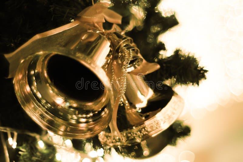Campanas de oro con un arco rojo en fondo brillante del bokeh de la falta de definición del árbol de navidad fotos de archivo