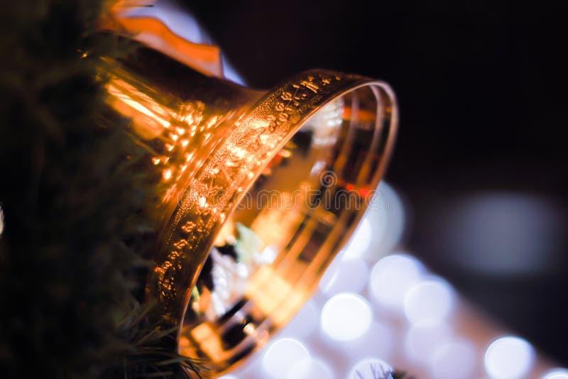 Campanas de oro con un arco rojo en fondo brillante del bokeh de la falta de definición del árbol de navidad fotos de archivo libres de regalías