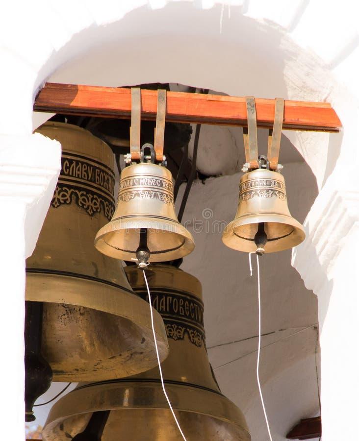 Campanas pequeñas y grandes en la iglesia rusa blanca imagenes de archivo