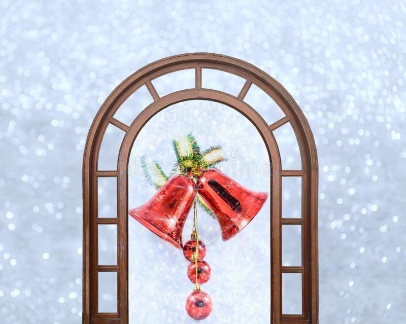 Campane di Natale con l'arco sui fiocchi di neve brillanti del fondo immagini stock libere da diritti