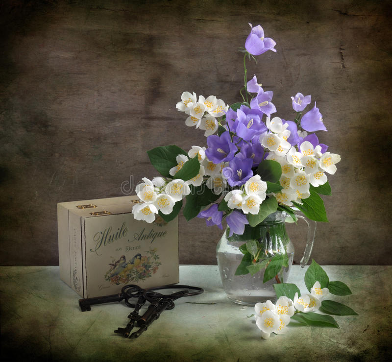 Campanellis and jasmin. The bouquet of campanellis and jasmin is costed in a glass vase, alongside keys and small box stock photo