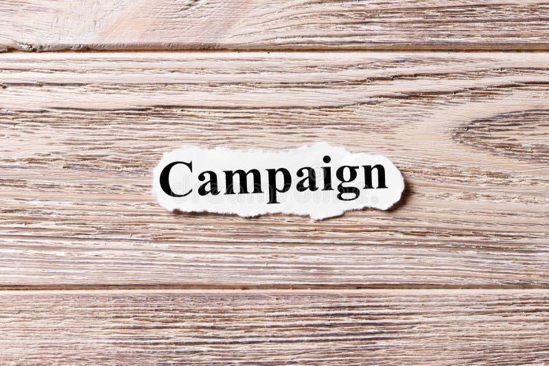 Campanha da palavra no papel Conceito Palavras da campanha em um fundo de madeira imagens de stock royalty free