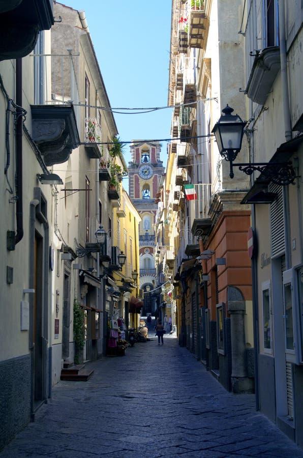 Campanile della chiesa e della lanterna all'estremità della via stretta a Sorrento, Italia immagini stock