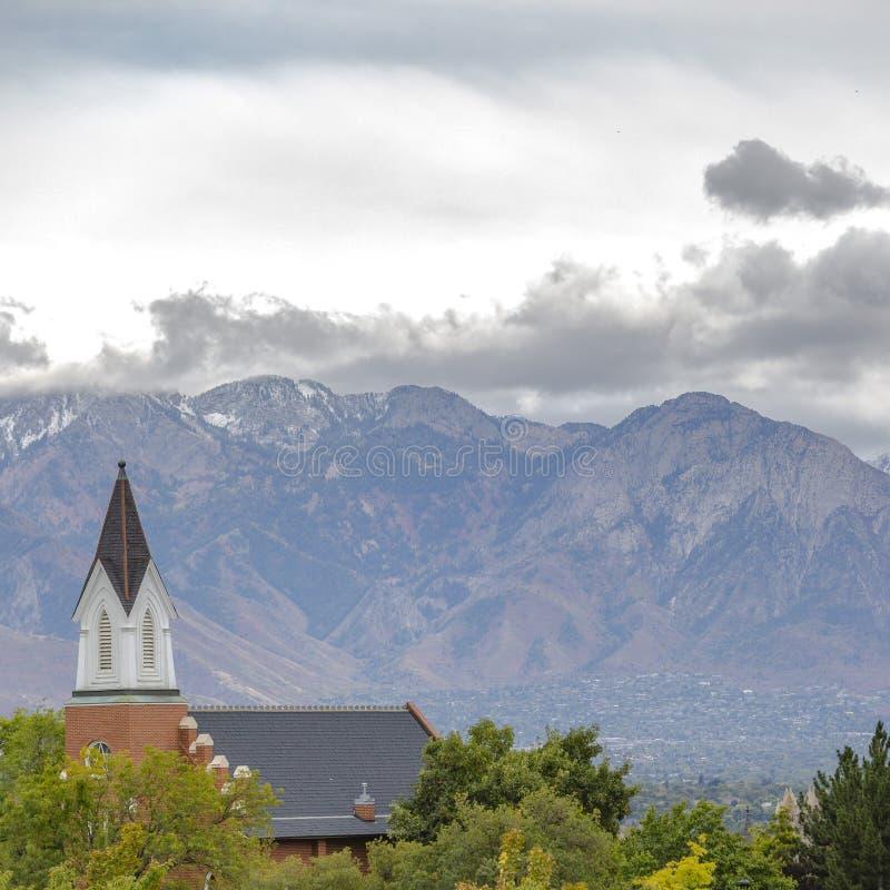 Campanile e tetto della chiesa sopra gli alberi verdi fertili immagini stock libere da diritti