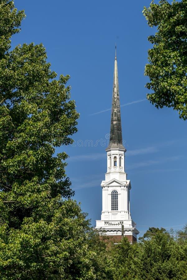 Campanile pittoresco della chiesa del campanile della chiesa di comunità del primo piano sopra gli alberi fotografia stock libera da diritti
