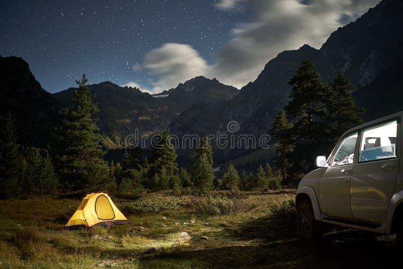 Campant avec une voiture, tente jaune la nuit avec le clair de lune au secteur de montagne photos stock