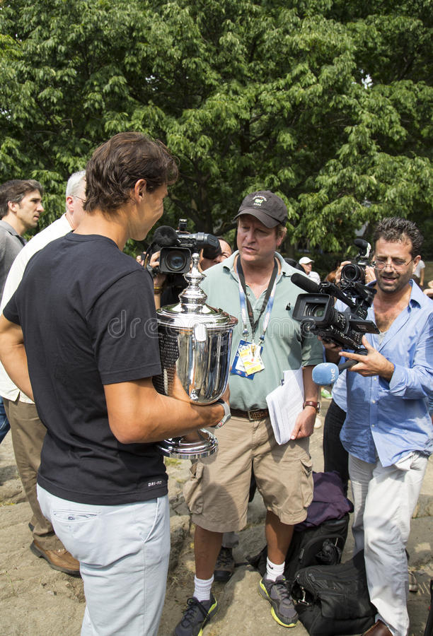 Campeão Rafael Nadal do US Open 2013 com o troféu do US Open cercado por journalistas durante a entrevista no Central Park fotos de stock