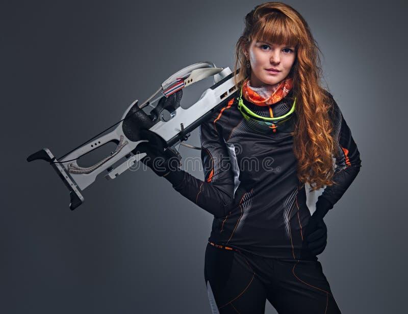 Campe?o f?mea do Biathlon do ruivo que aponta com uma arma competitiva fotografia de stock royalty free