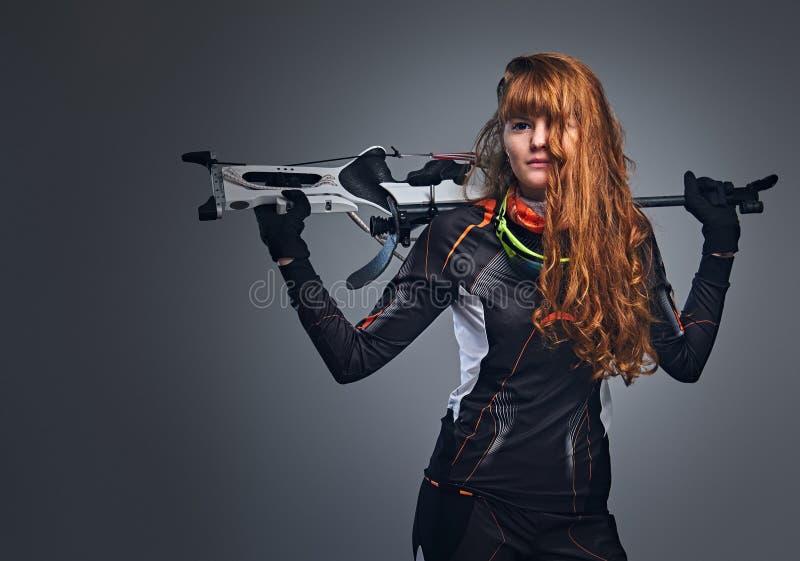 Campe?o f?mea do Biathlon do ruivo que aponta com uma arma competitiva imagens de stock