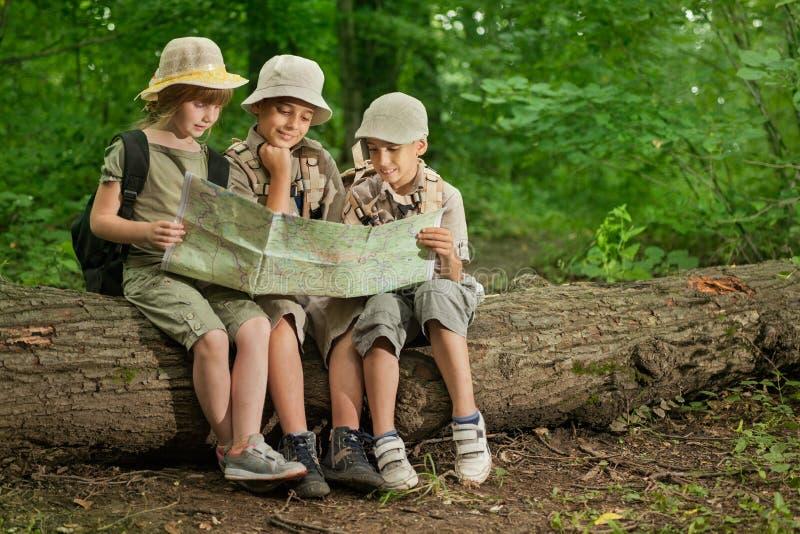 Campeggi estivi, bambini dell'esploratore che si accampano e mappa colta in foresta immagini stock