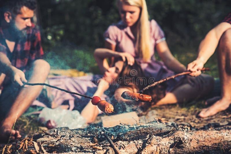 Campeggio di notte di estate Cottura delle salsiccie per la cena nel campo Ha offuscato due coppie che si siedono dal fuoco di ac fotografia stock libera da diritti