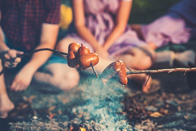 Campeggio di notte di estate Cottura delle salsiccie sui bastoni sopra le fiamme di fuoco di accampamento Due coppie che si siedo immagini stock
