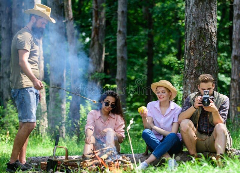 Campeggio e fare un'escursione Viandanti della società che si rilassano al fondo della foresta di picnic Passi il grande tempo su fotografia stock