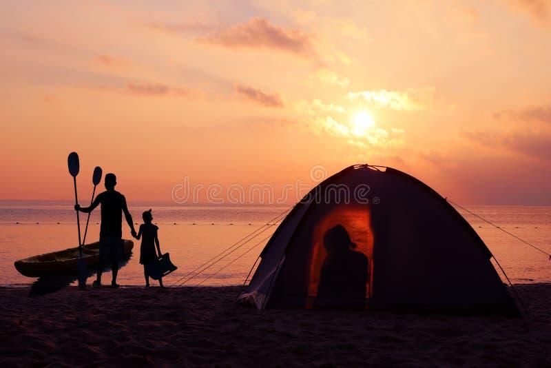 Campeggio e kayak della famiglia sulla spiaggia con il tramonto rosso del cielo fotografia stock