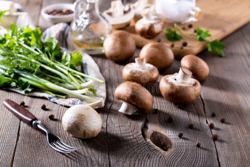 Campeonatos, dill, salsa, cebolas verdes em uma mesa de madeira Produtos para a preparação de pratos em cogumelos foto de stock