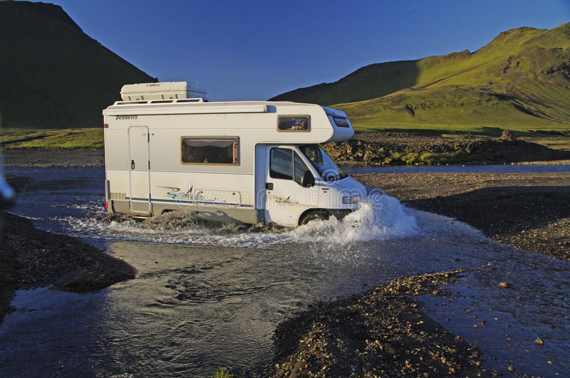 Camper crossing ford, Iceland stock image